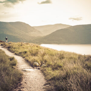 A Caucasian person is hiking through Ben Lomond by Loch Lomond, Scotland.  The person is on a dirt path with long grass on each side.  The sky is pale yellow with a few clouds.  There are dark mountains in the background and a lake in between the path and the mountains.